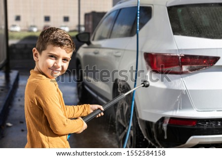 Little kid cleaning a car with a high pressure hose #1552584158