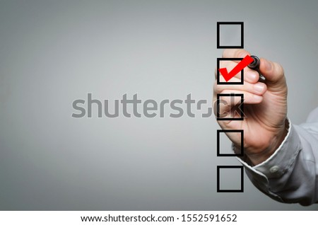 Blank checklist on the whiteboard with businessman hand drawing a red check mark in the check box