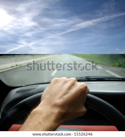 a closeup of steering wheel and a hand of a man in a car #15526246