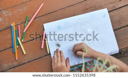 Child draws a pencil drawing of the house and his family. New home. #1552635398