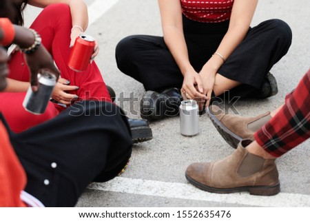 Cropped stock photo of unrecognizable hipsters relaxing on the ground with cans of drink.