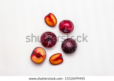 Ripe large purple plums. Fresh whole fruits, half sliced, seeds. Isolated on white background, copy space, top view #1552699445