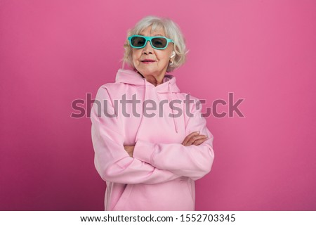 Cool old woman in funny green sunglasses posing on camera. Hands crossed. Wear pink hoody. Stylish modern grandma. Isolated over pink background