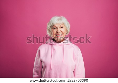 Happy cheerful positive old woman smiling wide and look straight on camera. Stand straight. Modern stylish senior model with grey hair. Isolated over pink background #1552703390
