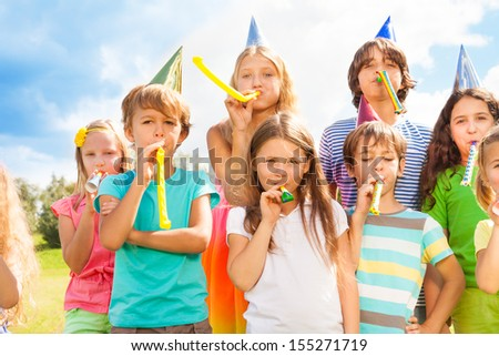 Many beautiful kids outside on a birthday party blowing noisemakers horns and twisted whistles #155271719
