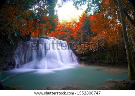 Hot Springs Onsen Natural Bath Surrounded by red-yellow leaves. In fall leaves fall .Waterfall among many foliage, In the fall leaves Leaf color change.soft focus. Huai Mae Kamin waterfall.