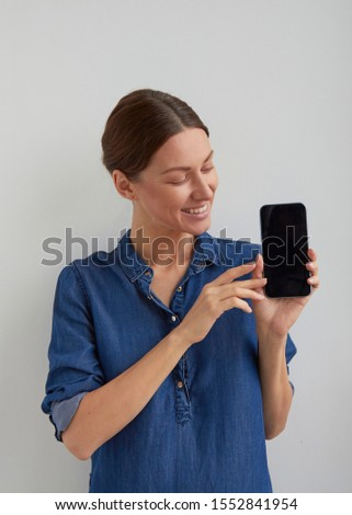Isolated happy pleased young brunette tucked back hair woman with smile in blue jeans shirt holds and promotes phone in hand and shows something by fingers on black screen on white background #1552841954