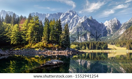 Impressive Autumn landscape during sunset. The Fusine Lake in front of the Mongart under sunlight. Amazing sunny day on the mountain lake. concept of an ideal resting place. Creative image. #1552941254