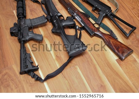Various automatic and semi-automatic guns on the floor, indoor close-up #1552965716