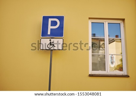 "Sign ""parking for disabled"" on the background of the house, near the window #1553048081"