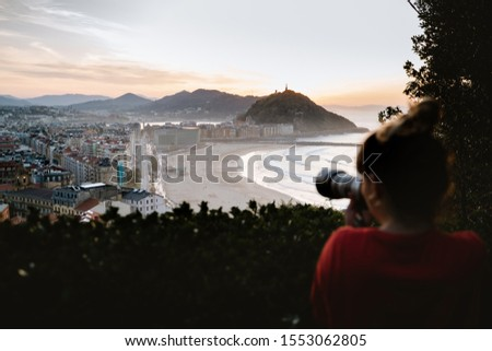 Young tourist girl taking a photo of San Sebastian from Mount Ulia during sunset #1553062805