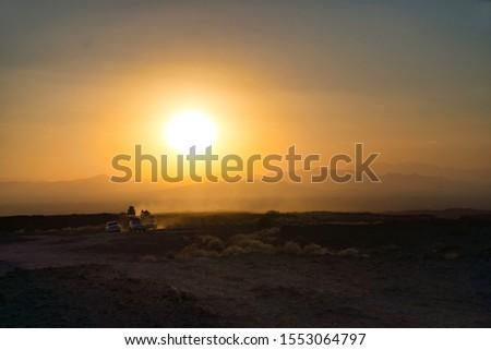 Afar Region, Ethiopia - January 01, 2019: TSafari cars going to the Erta Ale Volcano in Afar Region, Ethiopia at sunset, moving over the Danakil desert. #1553064797