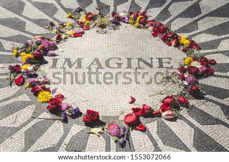 Landscape view of John Lennon's memorial located at Central Park, New York surrounded by colorful flowers left by fans and tourists.  Imagine can be read on it. #1553072066