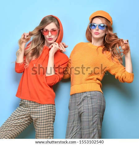 Fashionable woman in stylish outfit, makeup having fun dance. Two happy blonde redhead tomboy girl, trendy orange jumper, hoody, fashion hair. Cheerful sister friend, funny colorful concept #1553102540