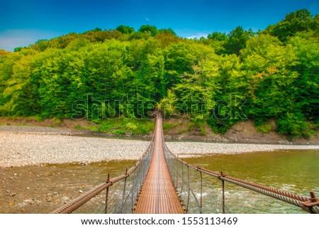 Iron suspension bridge. A suspension bridge leads over a mountain river #1553113469