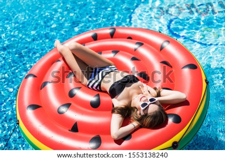 Young girl having floating with watermelon and taking sun in summer vacation. Vacation concept #1553138240
