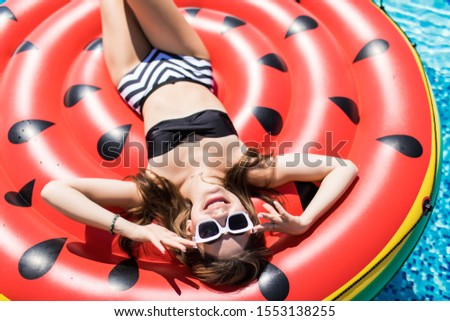 Young girl having floating with watermelon and taking sun in summer vacation. Vacation concept #1553138255