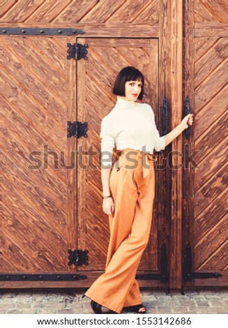 High waisted trousers. Woman attractive brunette wear fashionable clothes. Femininity and emphasize feminine figure. Girl wear loose high waisted pants. Fashion shop. High waisted pants fashion trend. #1553142686