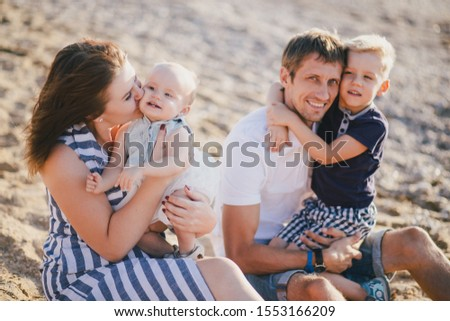 Happy family with two kids having fun near sea at the beach.  #1553166209
