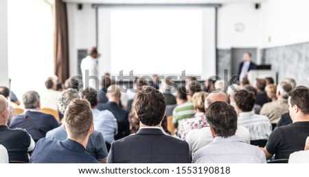 I have a question. Group of business people sitting at the chairs in conference hall. Businessman standing up asking a question. Conference and Presentation. Business and Entrepreneurship. #1553190818