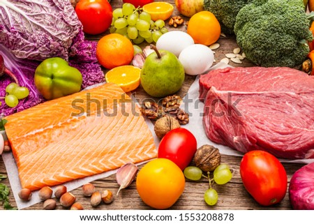 Trending paleo/pegan diet. Healthy balanced food concept. Set of fresh products, raw meat, salmon, vegetables and fruits. Old wooden boards background #1553208878