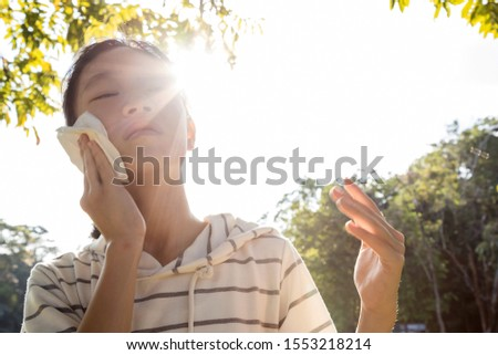 Asian child girl wiping sweat on her face with tissue paper suffer from sunburn very hot in summer weather problem feel faint, tired female teenage with heat stroke,high temperature on sunny day Royalty-Free Stock Photo #1553218214