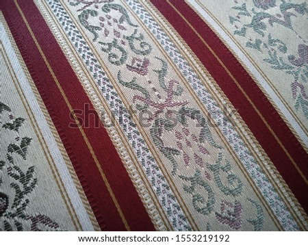 A sample of dense fabric for upholstery of upholstered furniture. The pattern of floral and floral elements in beige shades is combined with wide dark red stripes #1553219192