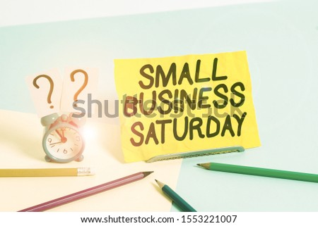 Text sign showing Small Business Saturday. Conceptual photo American shopping holiday held during the Saturday Mini size alarm clock beside stationary placed tilted on pastel backdrop. #1553221007