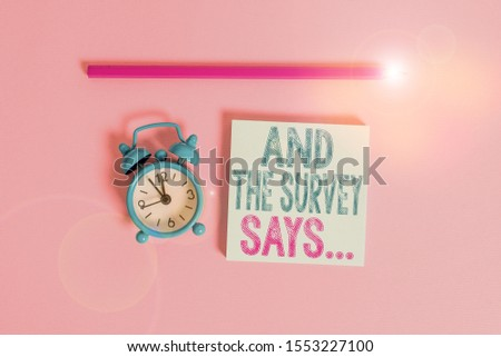 Word writing text And The Survey Says. Business concept for doing poll and bring the results discuss with others Metal vintage alarm clock wakeup blank notepad marker colored background. #1553227100