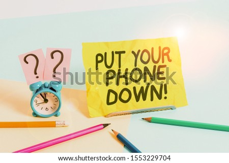 Text sign showing Put Your Phone Down. Conceptual photo end telephone connection saying goodbye caller Mini size alarm clock beside stationary placed tilted on pastel backdrop. #1553229704