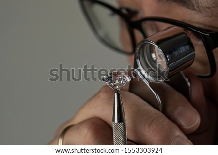 Man jeweller examines polished diamond through magnifier. Buyer checking diamond. Cut and polished diamond. Diamond jewellery under grading. Jeweller looking through loupe. #1553303924