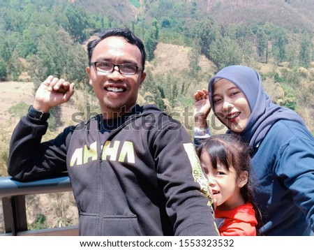 Probolinggo,East Java / Indonesia - July 29 th 2019: A husband and wife and daughter are taking pictures with the background of a beautiful hill #1553323532