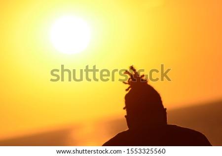 Rastafari guy enjoying the sunset #1553325560