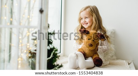 little girl with a plush deer sitting on the window. A child looks out the window and is waiting for Christmas, Santa Claus #1553404838