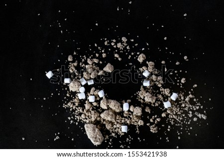 black food background with splashes of paste and marshmallow as stars planet in space #1553421938