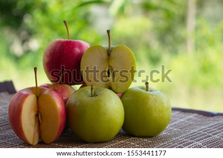 The red apples and the green apples are placed on the table, the background is a hazy lawn. #1553441177
