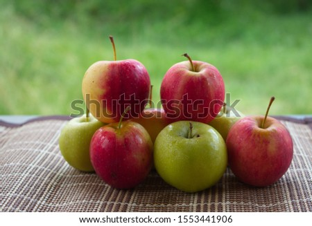 The red apples and the green apples are placed on the table, the background is  lawn. #1553441906
