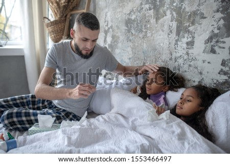 Two sick daughters. Two sick daughters lying in bed while father measuring body temperature #1553466497