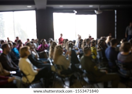 Blurred photo of people at the training. Workshop with lots of people. #1553471840