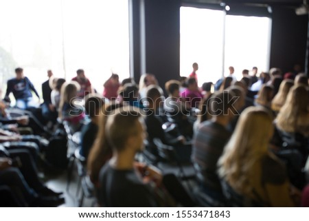 Blurred photo of people at the training. Workshop with lots of people. #1553471843