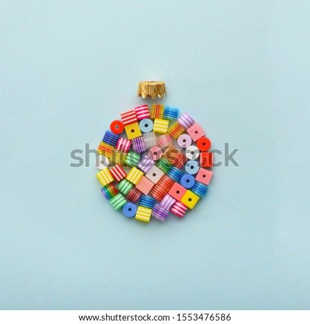 Christmas Bauble made of decoration elements on blue background. Flat lay. Contemporary design. Contemporary art. Creative conceptual and colorful collage. #1553476586