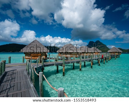 Luxury overwater villas on blue lagoon, white sandy beach and Otemanu mountain at Bora Bora island, Tahiti, French Polynesia #1553518493