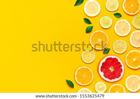 Flat lay composition with slices of fresh lemon orange grapefruit lime green leaves on yellow background top view copy space. Citrus Juice Concept, Vitamin C, Fruits. Creative summer background #1553625479