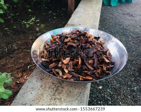 Brown Deep Fried Coconut in a steel plate kept on short wall. #1553667239