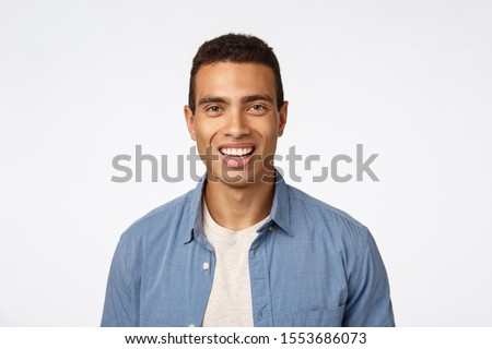 Cheerful, friendly handsome young tanned man in blue shirt over t-shirt, laughing, smiling happy as looking camera with enthusiastic, amused expression, promote something funny and joyful #1553686073