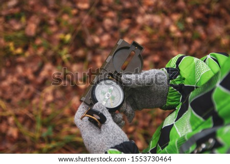 The child is guided by a compass in the woods. It's raining. Autumn. A man is lost, looking for his way home. #1553730464