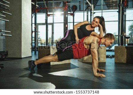 A group of muscular athletes doing workout at the gym. Gymnastics, training, fitness workout flexibility. Active and healthy lifestyle, youth, bodybuilding. Training upper and lower body. Support. #1553737148