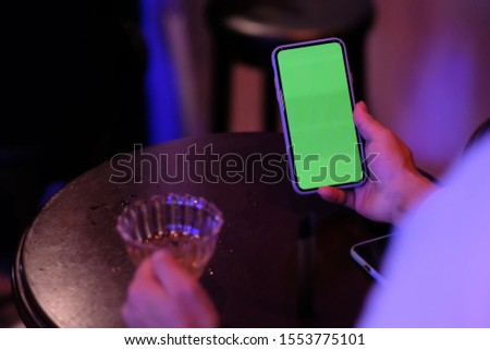 over shoulder of one man holding green screen phone at bar. blurred wooden table and cocktail glass background. #1553775101