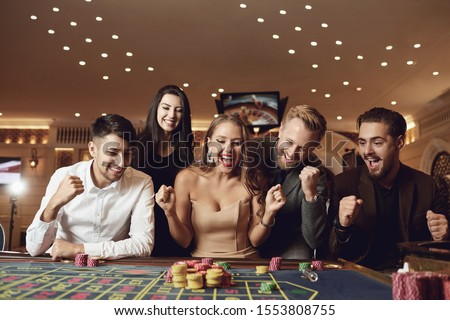 Happy people are betting in gambling at roulette poker in a casino Royalty-Free Stock Photo #1553808755