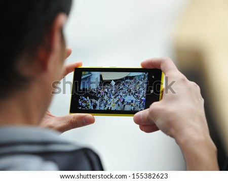 BANGKOK - JUN 30: A passerby uses a smartphone to capture an anti-government rally on Jun 30, 2013 in Bangkok, Thailand. The protesters known as V for Thailand call for the government to be removed. #155382623